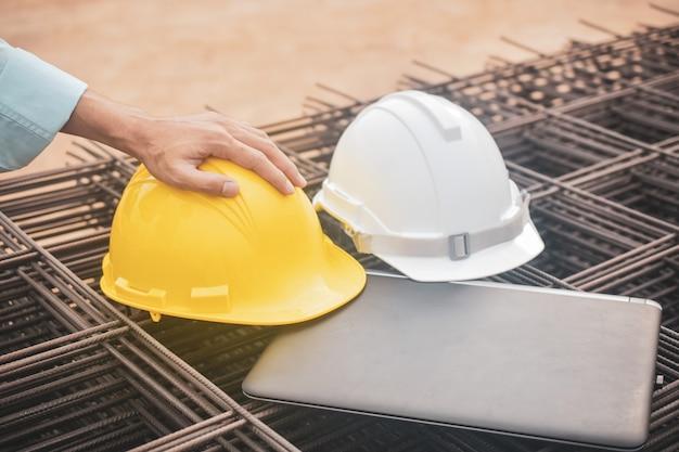 Cerrar el casco en la computadora portátil en el sitio de construcción de bienes raíces