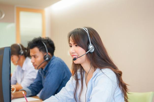 Cerrar en centro de llamadas mujer trabajo con empleado étnico diverso en sala de monitor de operación