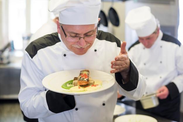 Cerrar el chef oliendo el plato después de cocinar