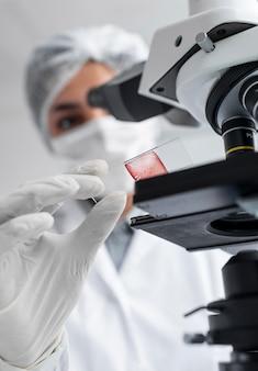 Cerrar científico borrosa trabajando con portaobjetos de vidrio