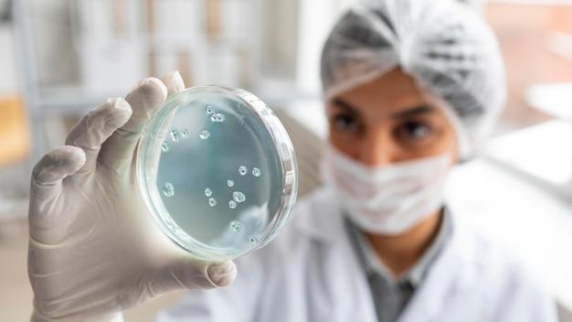 Cerrar científico borroso sosteniendo placa de petri