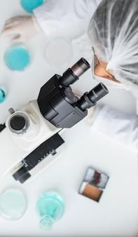 Cerrar científico mirando a través de la lente ocular
