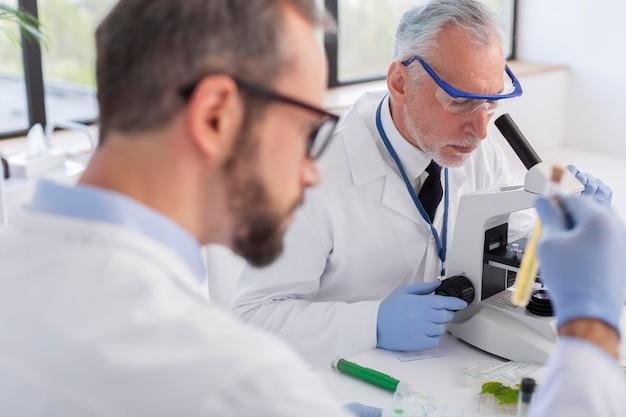 Cerrar científico que trabaja con microscopio