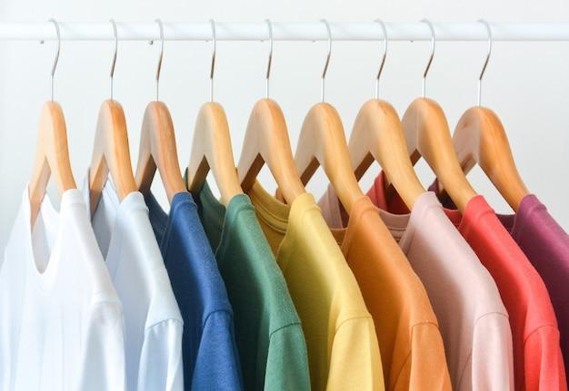Cerrar colección de camisetas de color pastel colgadas en la percha de madera en el armario o perchero sobre fondo blanco.