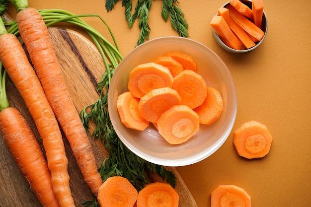 Cerrar la composición con rodajas y zanahorias frescas maduras