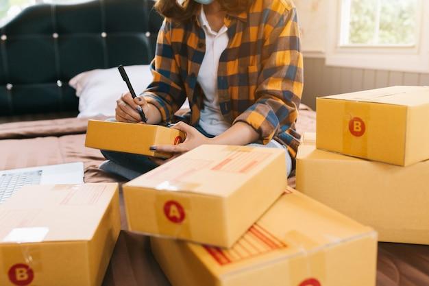 Cerrar compras en línea las mujeres jóvenes inician pequeños negocios en una caja de cartón en el trabajo.