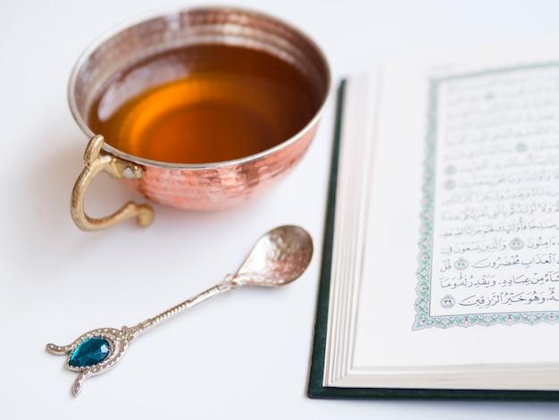 Cerrar el corán abierto con taza de té