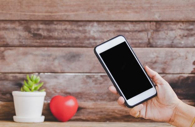 Cerrar el corazón rojo de san valentín hermoso con teléfono inteligente imitan para arriba en el fondo de madera rústica