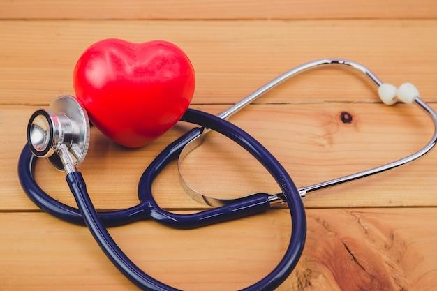 Cerrar corazón rojo y un steythoscope en mesa de madera vieja
