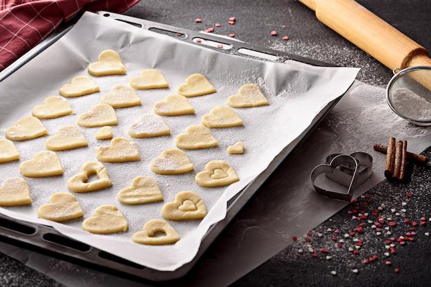 Cerrar corazones de mantequilla para galletas caseras en una bandeja para hornear sobre fondo oscuro