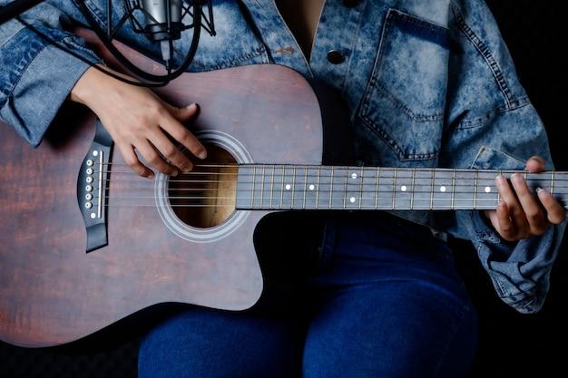Cerrar los dedos de la mujer sosteniendo mediador con una guitarra grabando una canción en el estudio de grabación
