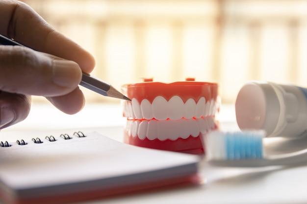 Cerrar la dentadura postiza con pasta de dientes cepillo de dientes en el fondo borroso.