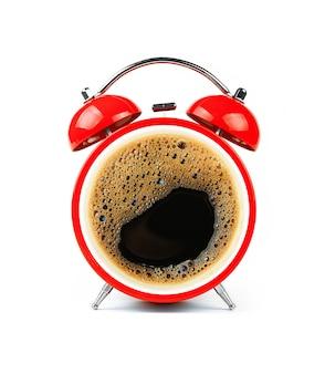 Cerrar un despertador retro rojo con cara de espuma de taza de café negro, aislado en blanco, ángulo bajo, vista frontal
