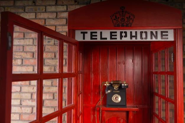 Cerrar detalle de cabina telefónica pública roja con teléfono antiguo interior y puerta abierta