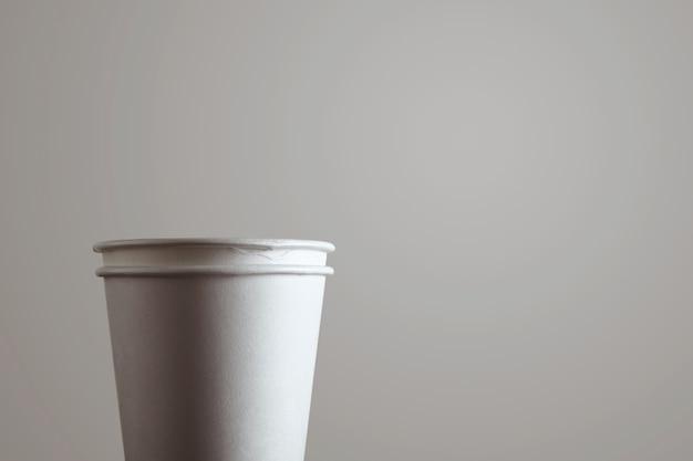 Cerrar detalle de dos vasos de papel para llevar en blanco aislado sobre fondo blanco.