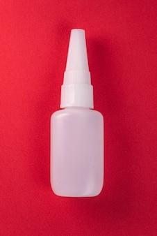Cerrar detalles de una botella de pegamento aislado