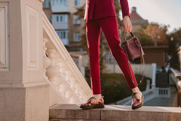 Cerrar detalles de moda de mujer elegante en traje morado caminando en la calle de la ciudad, tendencia de moda de primavera verano otoño temporada con bolso, pantalones y zapatos de moda calzado