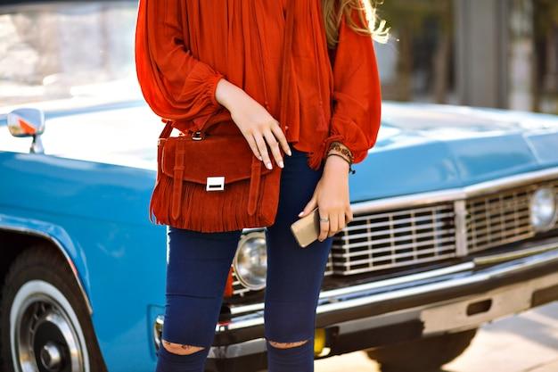 Cerrar detalles de moda de mujer posando frente a autos antiguos, atuendo moderno con estilo boho moderno, pantalones de mezclilla azul marino, blusa naranja y bolso, accesorios a juego, sosteniendo smartphone, primavera verano.