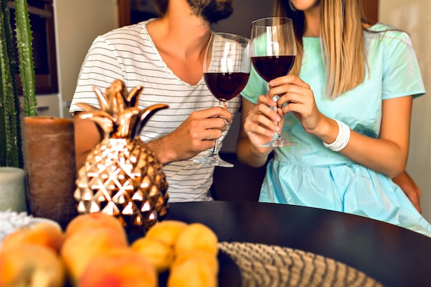 Cerrar detalles de la velada romántica de la bonita pareja bebiendo vino tinto y disfrutar del tiempo juntos, interior moderno y ropa elegante de moda.