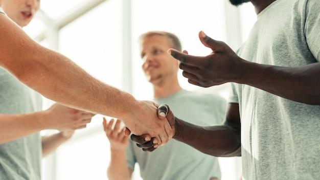 Cerrar dos camaradas dándose la mano de pie en un círculo de amigos