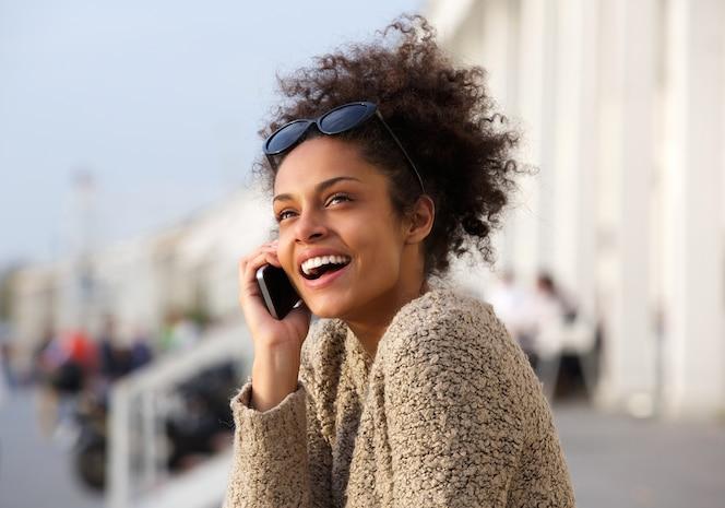 Cerrar el retrato de una mujer joven sonriendo con teléfono móvil