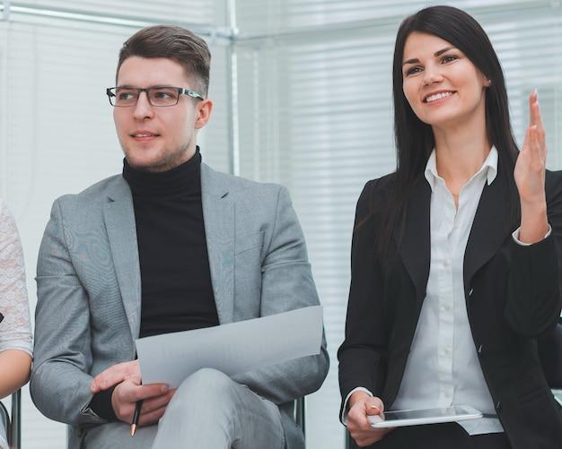 Cerrar empleados haciendo preguntas en una reunión de trabajo