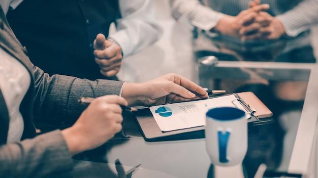 Cerrar la empresaria haciendo notas sobre un cuadro financiero