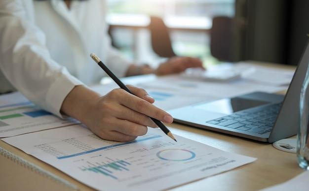 Cerrar empresaria usando calculadora y computadora portátil para calaulating finanzas, impuestos, contabilidad, estadísticas y concepto de investigación analítica