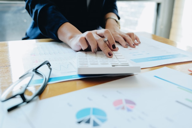 Cerrar empresaria usando calculadora y computadora portátil para hacer finanzas matemáticas en escritorio de madera en la oficina y el fondo de trabajo de negocios, impuestos, contabilidad, estadísticas y concepto de investigación analítica