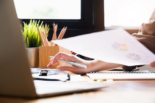 Cerrar empresaria usando la calculadora y la computadora portátil para hacer finanzas matemáticas en el escritorio de madera en la oficina y el fondo de trabajo de negocios, impuestos, contabilidad, estadísticas y concepto de investigación analítica