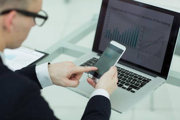 Cerrar empresario utiliza gadgets para verificar datos financieros
