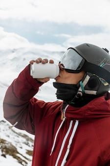 Cerrar esquiador bebiendo refrescos al aire libre