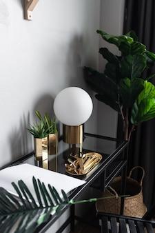 Cerrar esquina de trabajo con cactus artificial en jarrón de espejo dorado y libro sobre mesa de trabajo de vidrio