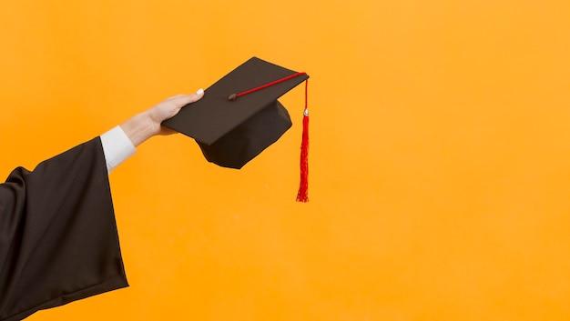 Cerrar estudiante graduado sosteniendo la tapa