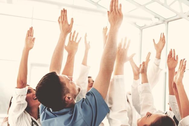 Cerrar feliz equipo de profesionales médicos con las manos arriba