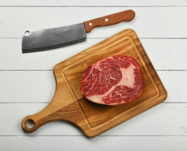 Cerrar un filete de ternera chuletón crudo veteado sobre una tabla de cortar de madera de roble marrón con un cuchillo, sobre una mesa de madera blanca, vista superior elevada, directamente encima