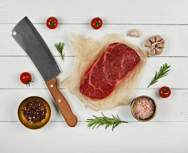 Cerrar un filete de ternera de solomillo crudo veteado sobre papel marrón, con cuchillo y especias, sobre mesa de madera blanca, vista superior elevada, directamente encima