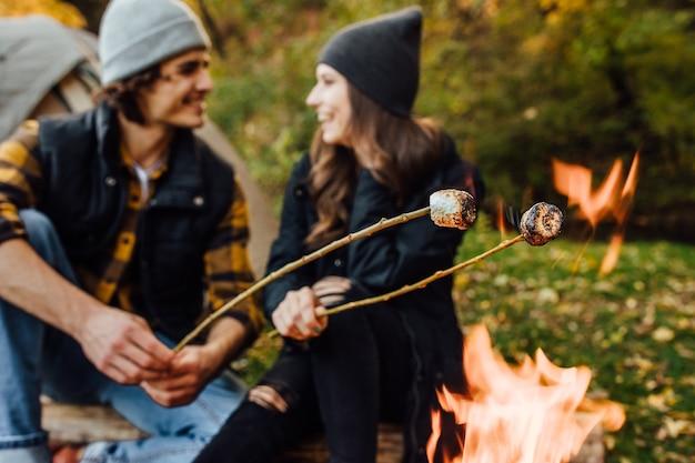 Cerrar foto de asar malvaviscos sobre el fuego cerca de la carpa en el camping