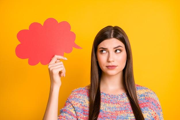 Cerrar una foto de una chica pensativa con una mente pensativa sostenga una tarjeta de papel roja pensar pensamientos decidir decisiones elegir una opción tratar de encontrar soluciones mirar sentir nervioso desgaste pullover aislado color brillante