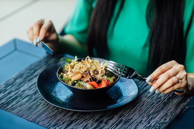 Cerrar foto, comida de restaurante, comer ensalada, sonriendo. hora de comer.