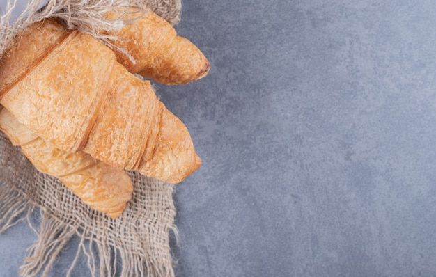 Cerrar foto de croissants recién horneados sobre fondo gris.