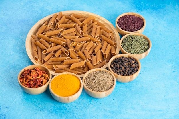Cerrar foto de crudo pasado marrón sobre tabla de madera y diversos tipos de especias sobre mesa azul.