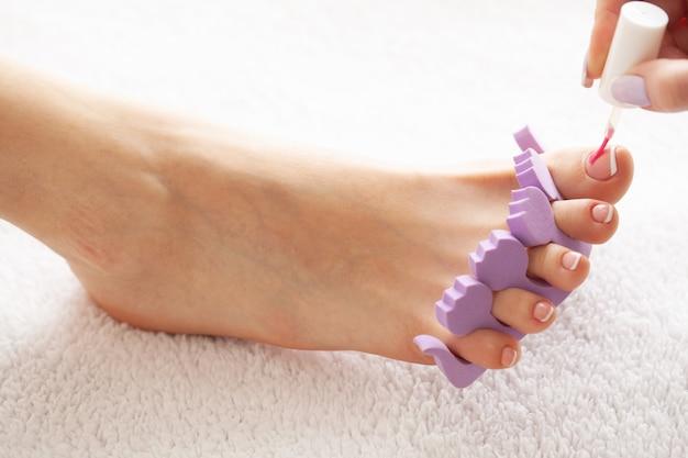 Cerrar la foto de una hembra de pies en el salón de spa en el procedimiento de pedicura