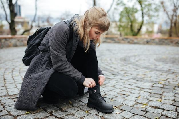 Cerrar foto de hermosa chica con cabello rubio inclinado en la calle para atar los cordones de los zapatos