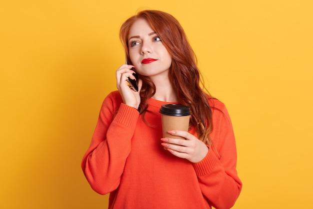 Cerrar foto hermosa dama abierta, sosteniendo una bebida caliente en un recipiente de papel aislado, hablando con el teléfono