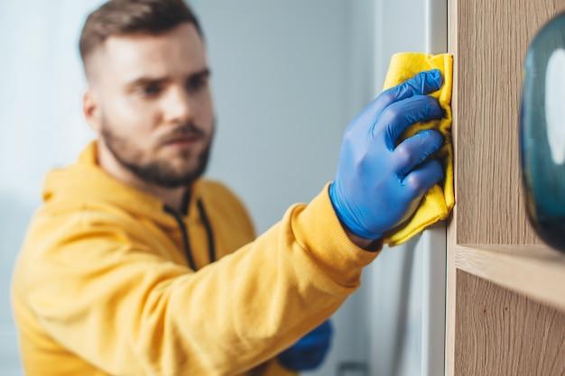 Cerrar foto de un hombre caucásico con barba con guantes azules está limpiando del polvo su casa