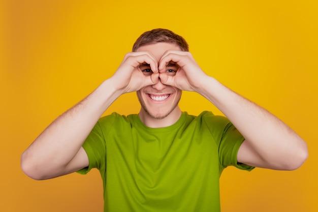 Cerrar foto de joven mostrar símbolo de dedo okey cerca de binoculares de ojos engañando a fondo amarillo brillante aislado