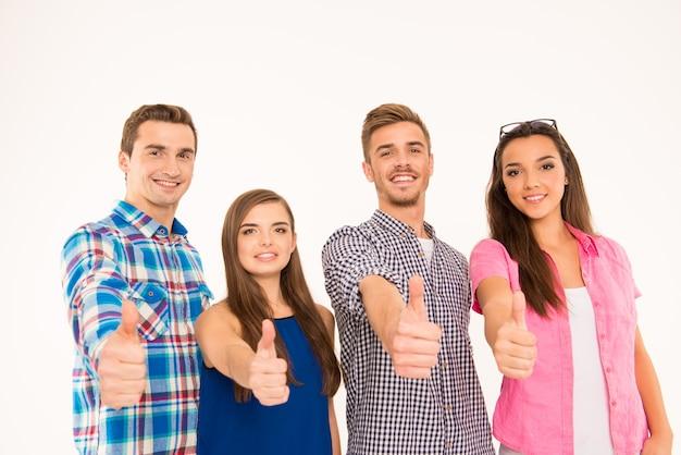 Cerrar foto de jóvenes alegres de pie mostrando los pulgares para arriba