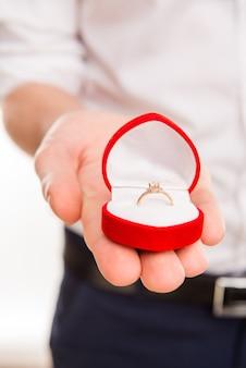Cerrar foto de la mano del hombre con caja con anillo de bodas