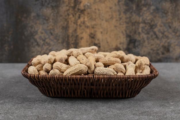 Cerrar foto del montón de cacahuetes con cáscara en la cesta